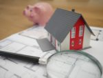 white and red wooden house beside grey framed magnifying glass