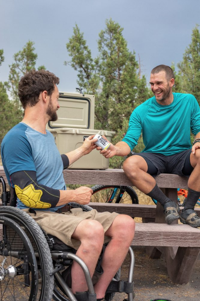 smiling man giving man beer can